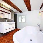 Badezimmer mit großer Wanne und freigelegten Deckenbalken. Bild: Knauf Aquapanel/Ekkehart Reinsch