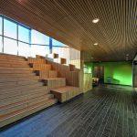 Das warm wirkende Holz der Außenanlagen wird innen bei (Sitz)Treppen, Decken und Wänden in Gemeinschaftsbereichen fortgeführt. Bild: Michael van Oosten