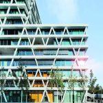 Mehrstöckiger Bürobau mit geometrischer Beton-Glas-Fassade. Bild: Huthmacher/Warema