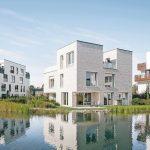 Wohnanlage mit kubischen weißen Mehrparteienhäusern an einem See. Bild: Stofanel Investment AG