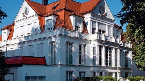 Zur Straße präsentiert sich die Villa mit weißen Säulen, Veranden und raumhohen Sprossenfenstern und Terrassentüren. Bild: Kneer-Südfenster