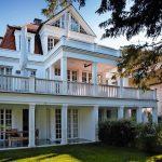 Zum Garten präsentiert sich die Villa mit weißen Säulen, Veranden und raumhohen Sprossenfenstern und Terrassentüren. Bild: Kneer-Südfenster