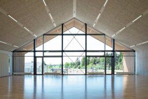 Im neuen, nachhaltig gebauten Mehrzweckhaus der dänischen Gemeinde Ikast sorgen Holzwolleleichtbauplatten mit verdeckt integrierter Lüftung für eine gute Akustik und ein gesundes Innenraumklima. Bild: Helene Høyer Mikkelsen