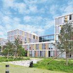 Langes, dreiflügeliges Gebäude vor begrünter Fläche. Bild: Richard Brink GmbH & Co. KG