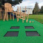 Spielplatz mit grünem Gummiboden und in den Boden eingelassenen Trampolienen. Bild: Melos GmbH
