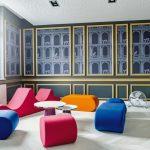 Goldfarbene Leisten machen aus dieser Wand ein Kunstwerk, das im schönen Kontrast zu den modernen Sitzmöbeln steht, nicht zuletzt auch farblich. Bild: Orac