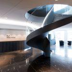 Seitenansicht einer Stahlwendeltreppe mit Glasgeländer und Stufen aus schwarzem Marmor. Bild: Spitzbart