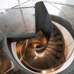 Draufsicht auf eine Stahlwendeltreppe mit Glasgeländer und Stufen aus schwarzem Marmor. Bild: Spitzbart