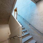 Eine lange Betontreppe führt, gesäumt von Sichtbetonflächen, bis ins dritte Untergeschoss