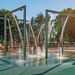Wasserspielplatz Norikusbucht: Im Bereich der Duschen und Bodenwasserfontäne wurde ein glatter, rutschsicherer Belag installiert. Er ist wasserdurchlässig, wodurch die Oberfläche rasch abtrocknet. Bild: Hackl Hofmann Landschaftsarchitekten