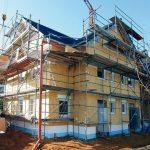 Baustelle eines Mehrfamilienhauses, mit Baugerüst und Kran. Bild: Saint-Gobain Isover GmbH