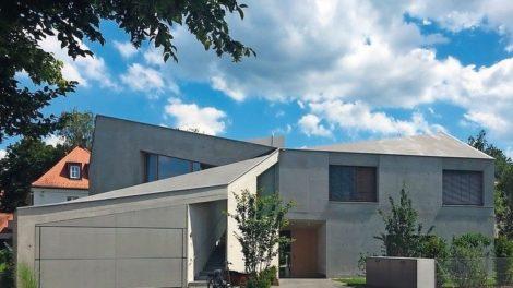 Links oben Baumzweig vor weißblauem Himmel über grauem Haus mit Kipptor.
