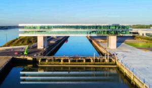Büroriegel mit Metallfassade als Brücke über den Fluss