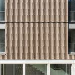 Als hoch wärmegedämmte Gebäudehülle wurde eine Vorhangfassade aus Weißtannenholz gewählt, die mit Lasur vorvergraut wurde und so den natürlichen Patinaeffekt vorwegnimmt. Bild: Lignotrend / Foto: Olaf Herzog, Waldkirch
