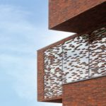 Glasfront mit unregelmäßig aufgeklebten Klinkerriemchen in der Backsteinfassade