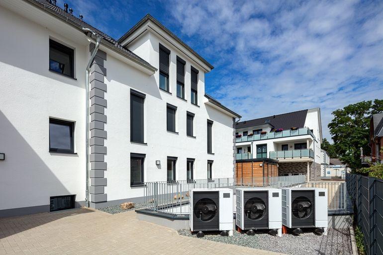 Weiße Hausfassade mit drei Luft/Wasser-Wärmepumpen-Außengeräten.