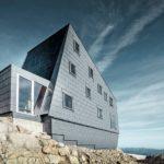 Graue Fassade aus Aluminiumverbund auf Felsen gebaut.