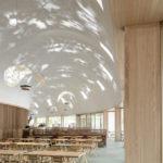 Lichter Raum mit Leuchten, die ein Sonnenstrahl-Muster auf die Decke projizieren