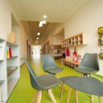 Auch in Fluren, Ankleidungs- und Kocharealen ist das Design mit hellen Räumen und Rot-/Grünakzenten erkennbar. Bild: © SWISS KRONO   Foto: tm studios