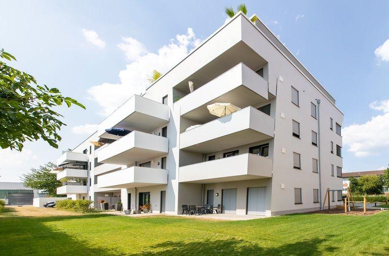 Fensterfalzlüfter für weißes Haus mit Balkonen.