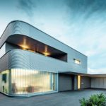Abgerundete Hausecke mit Aluminiumfassade und erleuchteten Innenräumen.