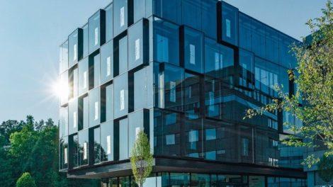 Blau verglastes Eckhaus gewährt Sonnenschutz.