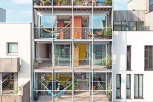 Rückseitige verglaste Fassade mit durchgängigen Balkonen auf jedem Stockwerk, Blick auf den Garten.