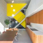 Esstisch vor gelber Treppenverkleidung.