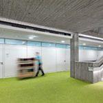 Grüner Boden mit Mann mit Rollcontainer vor weißen Systemtrennwänden.