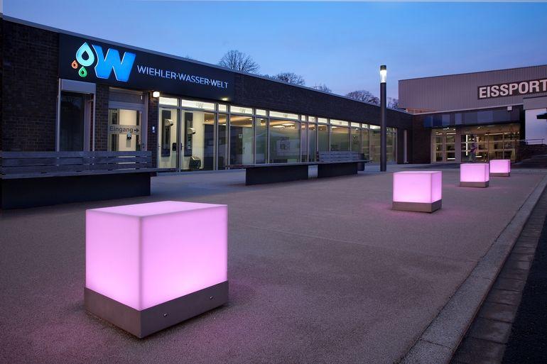 Kuben mit Licht beleuchten den Außenraum des Schwimmbads.
