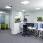 Büroarbeitsplatz mit Tisch und Stuhl auf hellgrauem Bodenbelag.