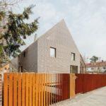 Hinter braunem Holzzaun helles Haus mit Holzfassade.