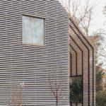 Hellgraue Holzfassade mit Fenster.