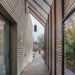 Holzfassade legt sich wie eine Pergola vor das Haus.