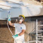 Arbeiter trägt Spritzbeschichtung auf Stahlträger auf, Sika Deutschland GmbH