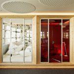 Nebeneinanderliegende Räume mit Glastüren. Links in Weiß, rechts in Rot gehalten. Bild: AKIM Photography